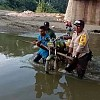 Bhabinkamtibmas Bantu Warga angkat Motor Seberangi Sungai